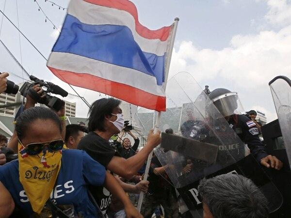 Manifestantes antigubernamentales se enfrentan a la policía antidisturbios cerca de la sede del Gobierno en Bangkok (Tailandia) este viernes.