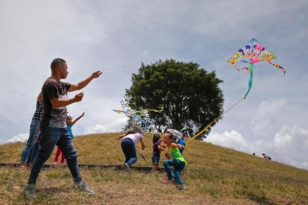 Muchas personas aprovecharon el feriado de este Jueves Santo para visitar el Parque de la Paz . En la foto, Javier Amador, vecino de Hatillo, vuela papalotes con sus hijos. Asegura que prefieren quedarse en San José porque hay mucho peligro en la playa. Fotos: Mayela López