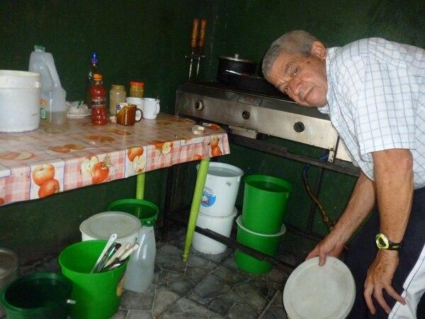 Enrique Sanabria, quien labora en una soda, muestra los recipientes donde guardan agua para lo básico.