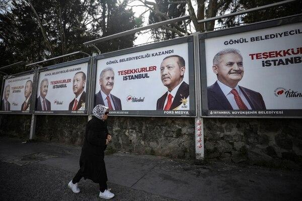 Una mujer pasa junto a los carteles que muestran a Binali Yildirim, a la derecha, el candidato a la Alcaldía de Estambul, el presidente de Turquía, Recep Tayyip Erdogan, del gobernante Partido de Justicia y Desarrollo (AKP) un día después de las elecciones locales en Estambul, el lunes 1°. de abril de 2019. Foto: AP