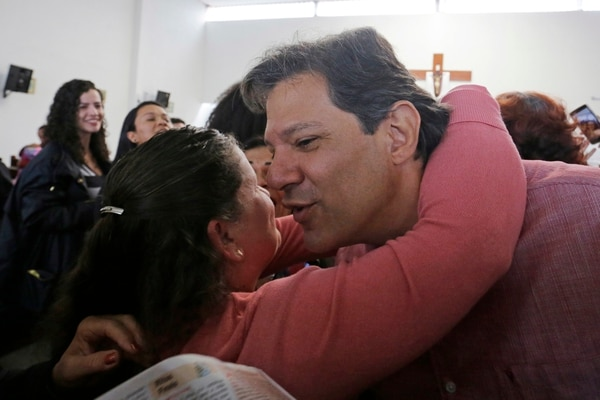 Brazil's presidential candidate for the Workers Party Fernando Haddad embraces a supporter during a mass celebrating the day of Our Lady of Aparecida in Sao Paulo, Brazil, Friday, Oct. 12, 2018. Haddad will face Jair Bolsonaro, the far-right congressman in a presidential runoff on Oct. 28.(AP Photo/Nelson Antoine)