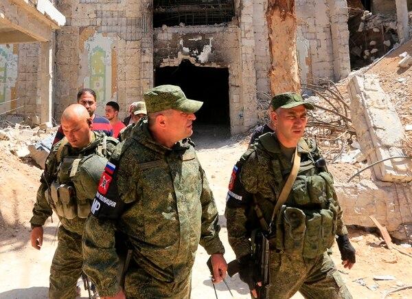 Policías militares rusos patrullaban en medio de edificios dañados en la ciudad de Duma, Siria, este lunes 16 de abril del 2018.