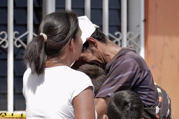 Juan Carlos Briones (padre de Joseph, uno de los fallecidos) se abraza con otros de sus hijos al llegar al lugar del crimen. Lo acompaña su compañera sentimental, Kattia Corea.