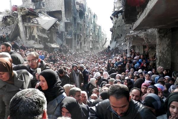Los residentes del campamento palestino ubicado en Yarmouk, hacen fila para recibir los suministros de alimentos, en Damasco, Siria.
