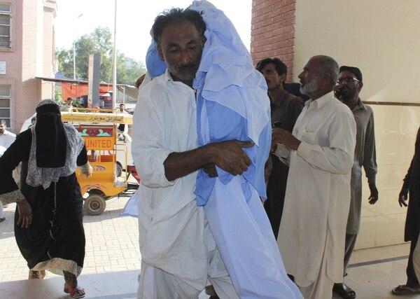 Un hombre lleva en brazos a una niña que resultó herida al caerle encima la pared de un colegio que se derrumbó en Sargodha (Pakistán) como consecuencia del teremoto de 7,5 grados.