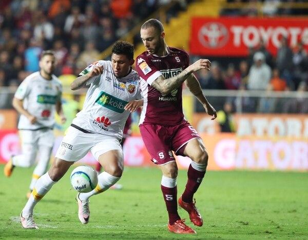 Henrique Moura marca al florense José Guillermo Ortiz, en el juego en que Saprissa derrotó a Herediano 1-0. Fotografía: John Durán