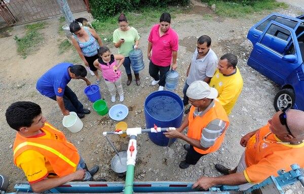Las filas con ollas, peroles y envases plásticos se hacían largas con cada viaje de los camiones cisterna. Estos repartieron agua ayer en varios sectores de Higuito de San Miguel de Desamparados. | GRACIELA SOLÍS