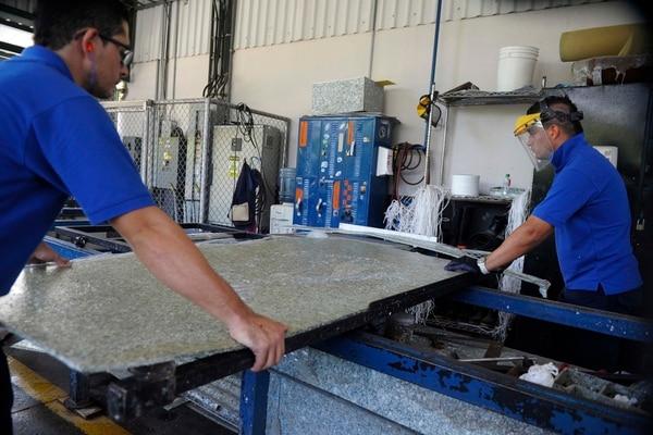 Alexánder Campos y Luis Araya cortan las láminas de Reciclam que serán llevadas a las cárceles para elaborar pupitres.