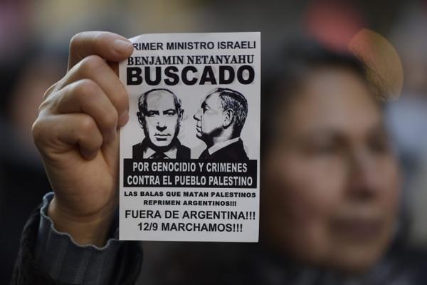 Un manifestante sostiene un afiche contra la visita del primer ministro israelí Benjamín Netanyahu a Argentina durante una protesta en las afueras de la embajada israelí en Buenos Aires.