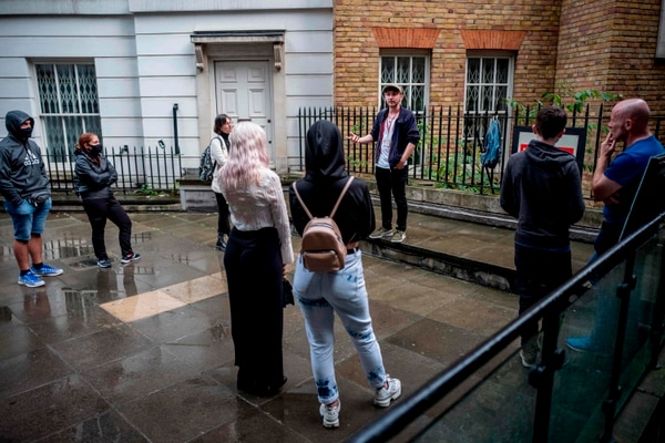El guía turístico Joel Robinson acompaña a un grupo de turistas en la ruta de Jack el Destripador, por las callejuelas de Londres. La mayoría de sus clientes, ahora, son residentes británicos. Foto: AFP