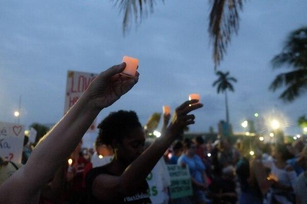 Varias personas sostienen velas durante una manifestación de protesta y vigilan en apoyo de la liberación y la reunificación de los niños migrantes fuera del Refugio Temporal de Homestead para Niños No Acompañados, en Homestead, Florida. Foto: AFP