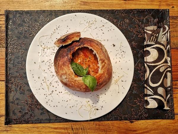 En esta crema de tomate abundan los aromas a hierbas y queso parmesano. Una delicia servida dentro de un pan tipo hogaza al cual le quitaron la miga. Foto: Osvaldo Calderón