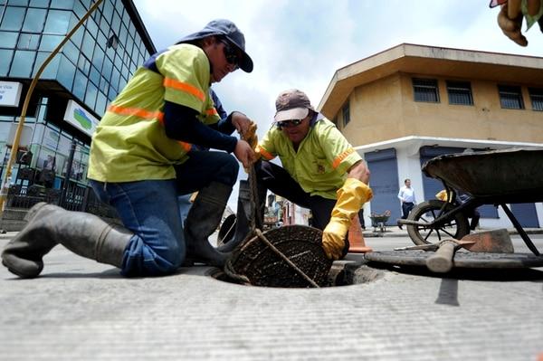 El 30 de setiembre, Rafael Barboza y Ricardo Mora ayudaban a sacar un trozo de tapa del alcantarillado en la jornada de limpieza de los desagües, luego de las inundaciones en el centro de San José. | JORGE NAVARRO