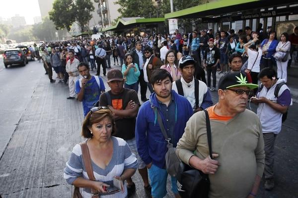 Una multitud espera algún medio de transporte en una calle de Santiago de Chile