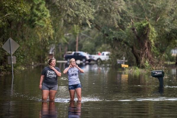 Holly Lands (izq.) y Morgan Lindsey caminan por una calle inundada durante el paso del huracán Irma cerca de Palatka, Florida.