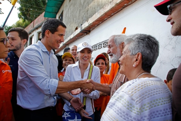 Venezuela's National Assembly President and self proclaimed interim President Juan Guaido, left, shakes hands with a man during a rally at the Municipality of El Hatillo, Caracas, Venezuela, Saturday, Sept 14, 2019. Guaido rejected allegations Friday that he has ties to an illegal armed group in Colombia, as officials launched an investigation based on photos appearing in social media purportedly showing him posing with members of the gang. (AP Photo/Leonardo Fernandez)