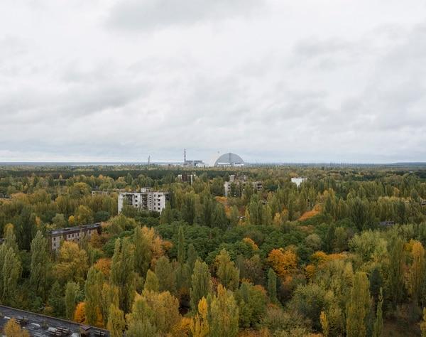 El paisaje urbano que rodea a la antigua planta de energía nuclear es cada vez más reducido y ha sido ocupado por un paisaje natural como se observa en esta imagen del 2017. En el centro el nuevo sarcófago que cubre el reactor 4. Foto: David McMillan.