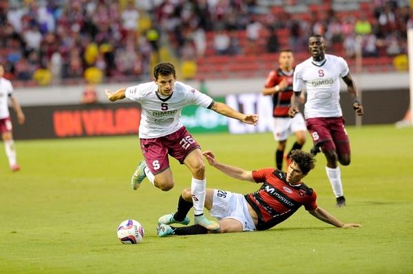 El volante alajuelense Ariel Rodríguez barrió al saprissista Daniel Colindres en un tramo del clásico disputado ayer en el Estadio Nacional.   MELISSA FERNANDEZ