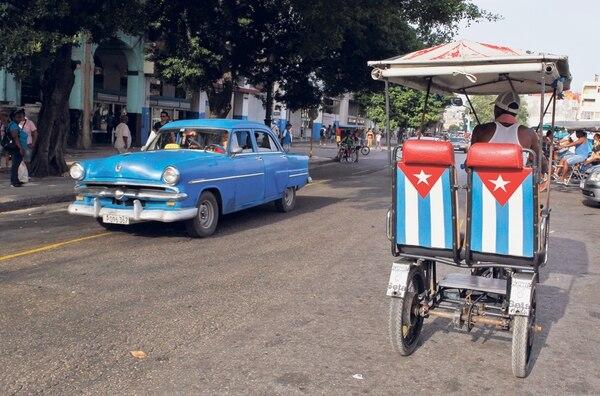 Un auto clásico cruzó frente a un bicitaxi este miércoles en La Habana, Cuba.