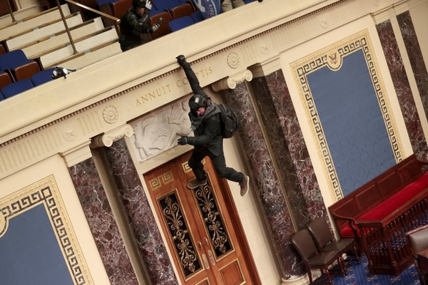 WASHINGTON, DC - JANUARY 06: A protester is seen hanging from the balcony in the Senate Chamber on January 06, 2021 in Washington, DC. Congress held a joint session today to ratify President-elect Joe Biden's 306-232 Electoral College win over President Donald Trump. Pro-Trump protesters have entered the U.S. Capitol building after mass demonstrations in the nation's capital. Win McNamee/Getty Images/AFP