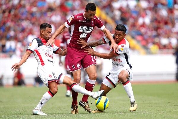 Mariano Torres dejó en el camino a los manudos José Luis Cordero (izquierda) y Luis Garrido (derecha) en un clásico disputado en el Estadio Nacional. Foto: Albert Marín.