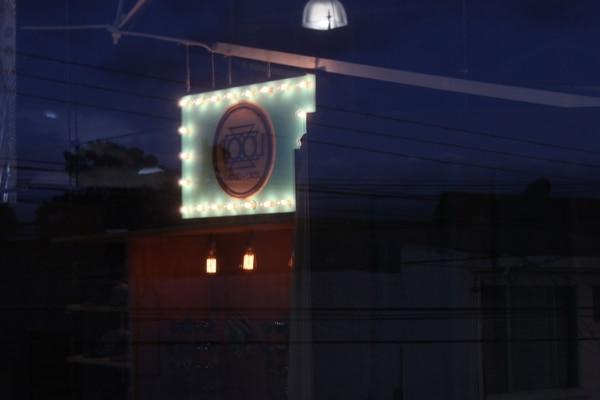 Letrero de Loop reflejado en los ventanales. Al fondo, las afueras de la Casa del Cuño.