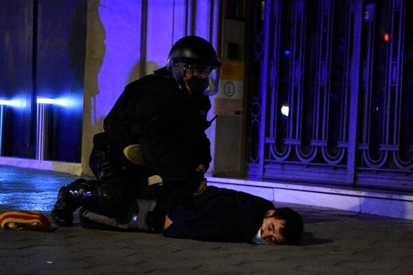 Un oficial de los Mossos d'Esquadra detiene a un manifestante tras los enfrentamientos en una manifestación contra el encarcelamiento del rapero español Pablo Hasel. Foto: AFP