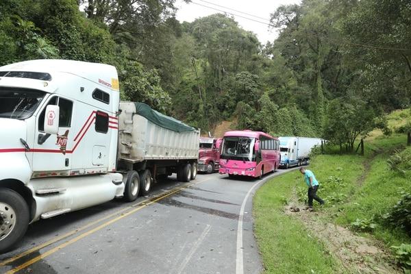 Varios camiones y un autobus de Tracopa se mantienen n medio del Cerro de la Muerte