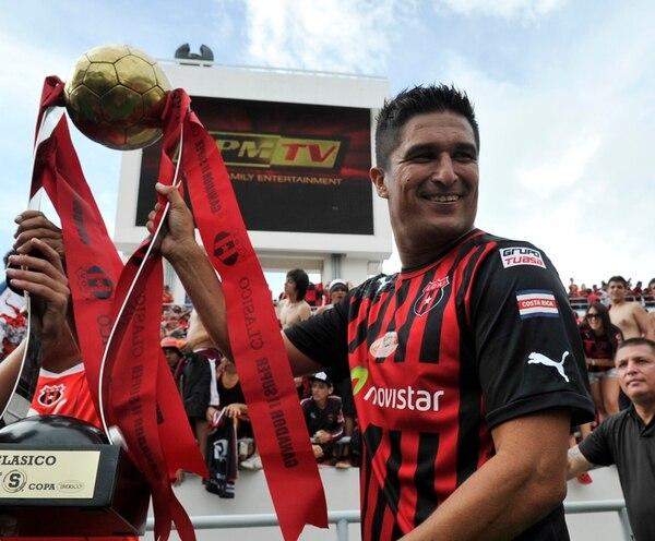 Cristian Oviedo muestra la segunda Copa Ibérico que obtiene la Liga. Al fondo, la feligresía manuda celebra el triunfo en el clásico. | CARLOS BORBÓN