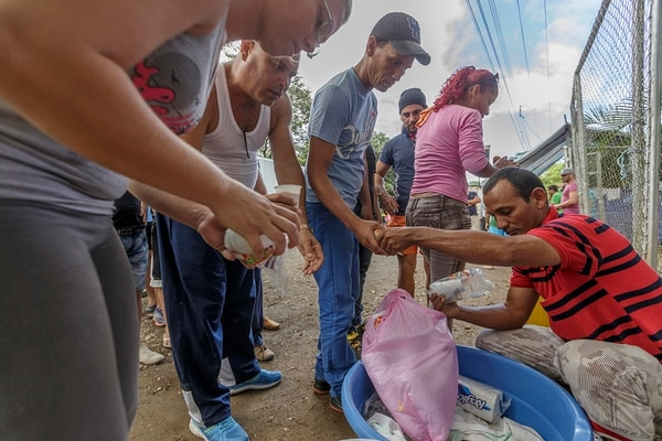 Varios lugareños ayudan con alimentación a los cubanos que están varados frente a la frontera con Nicaragua, cuyo gobierno les impide el tránsito hacia el norte.