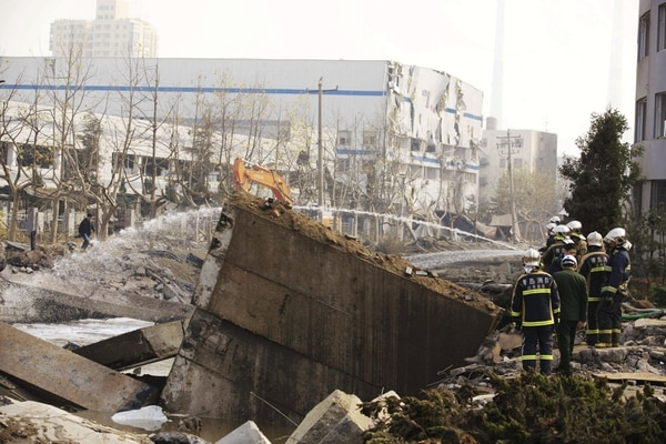 Miembros de los servicios de emergencia trabajan en el lugar donde se produjo la explosión de un oleoducto en la ciudad costera de Qingdao (China).