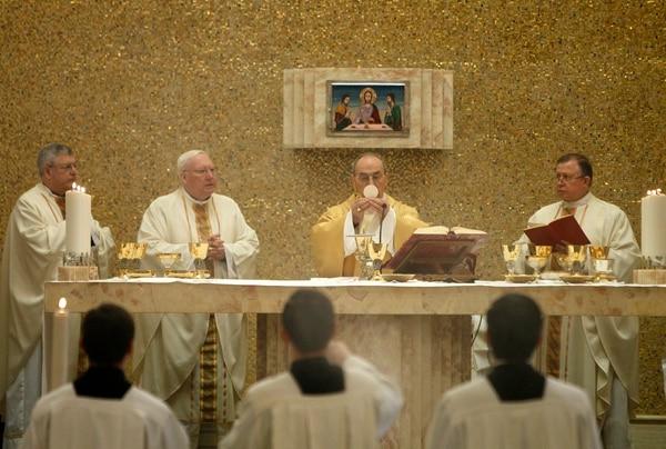 Velasio De Paolis (con la hostia), flanqueado por el entonces nuevo director general de los Legionarios de Cristo, Eduardo Robles (derecha), ofició una misa en la sede de la congregación en Roma, el 25 de febrero del 2015.