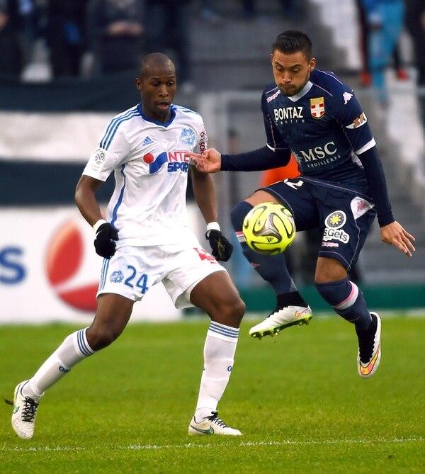 David Ramírez ante la marca del defensor francés del Olympique de Marsella Rod Fanni en un juego de la Liga 1.