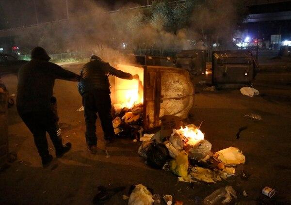 Manifestantes usaron depósitos de basura para bloquear una calle en Beirut, este martes 21 de enero del 2020.