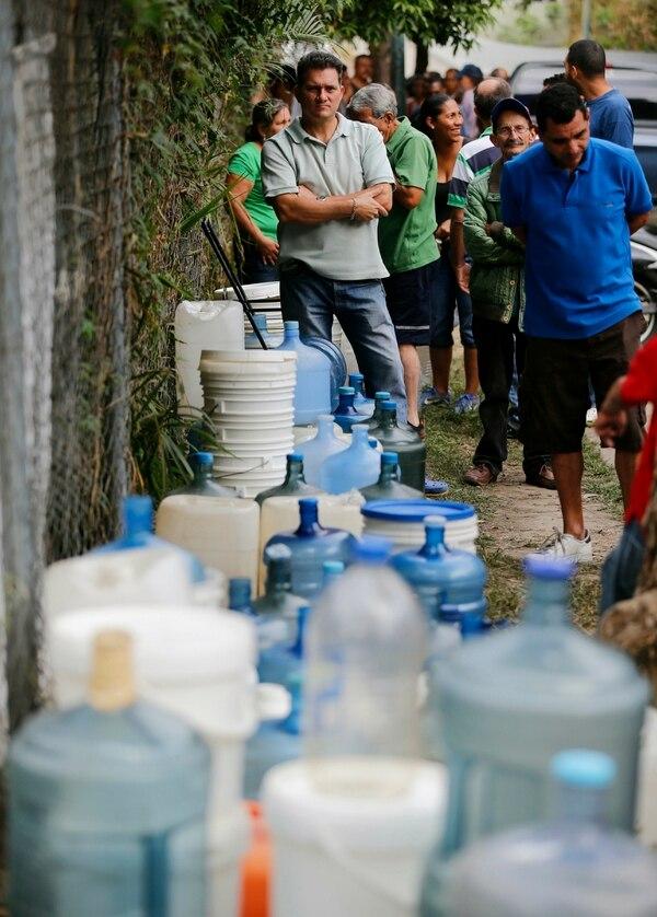 Venezolanos aguardaban para llenar recipientes con agua en una fuente pública cerca de Caracas, el 11 de marzo del 2019.