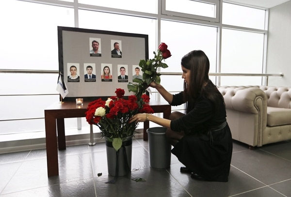 Una mujer coloca flores junto a las fotografías de sus compañeros, la tripulación del vuelo de la aerolínea Kogalymavia siniestrado en el Sinaí, en la sede de la compañía en Moscú, Rusia.