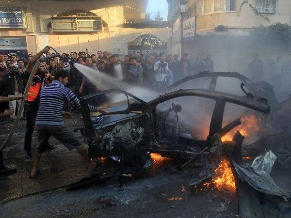 Los palestinoes extinguen el fuego del carro en el que viajaba el jefe de operaciones militares, Ahmaed Jaabari, blanco de un ataque aéreo israelí.   AFP