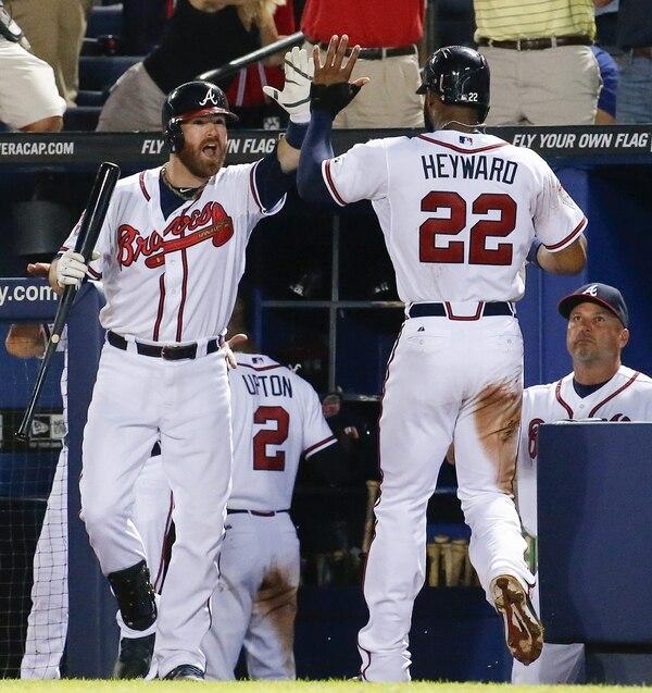 Jason Heyward, de los Bravos de Atlanta, es felicitado por el receptor Ryan Doumit tras anotar ante los Mets de Nueva York.