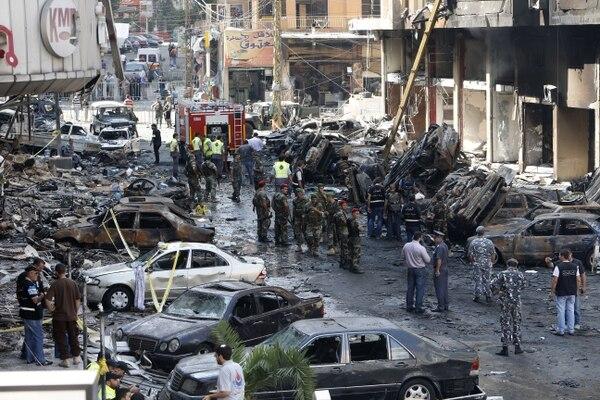 Un grupo de la policía inspecciona varios coches dañados tras explosión en Beirut.