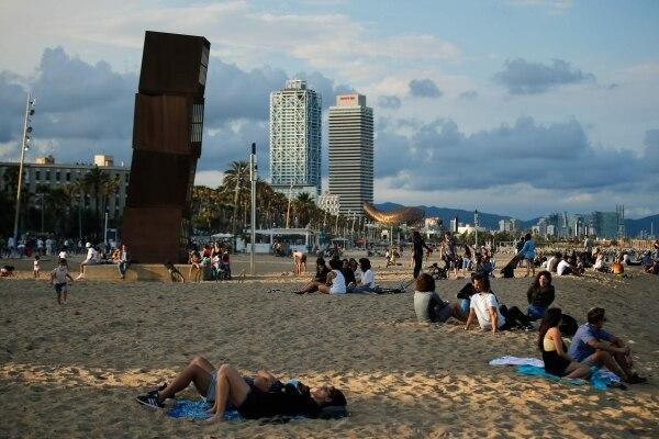Las personas disfrutan en la playa de la Barceloneta, en Barcelona, el 30 de mayo del 2020, mientras el país comienza a relajar las restricciones. Foto: AFP