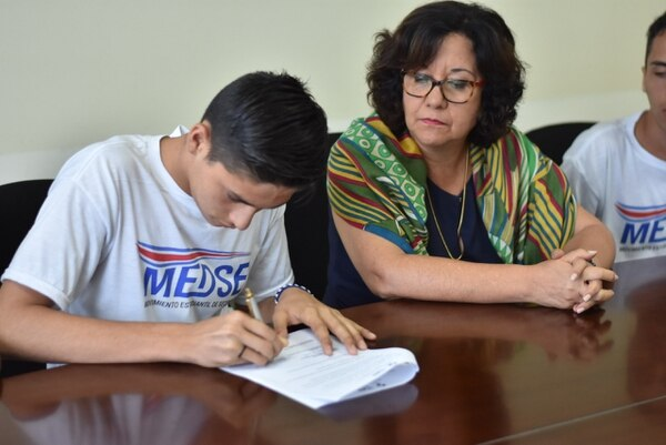 Momento en que uno de los estudiantes firman junto a la ministra Guiselle Cruz.