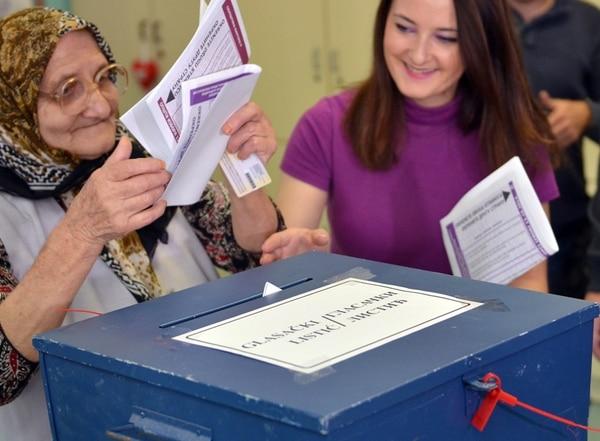 Una mujer deposita su voto en una urna de Sarajevo, Bosnia. | AFP