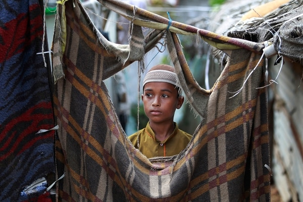 Un joven refugiado de la etnia rohingya se asoma por una alfombra que ha servido como pared en las afueras de la India.