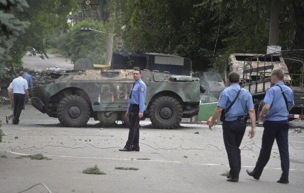 Varios policías ucranianos caminan delante de una barricada de prorrusos escapados de Mariupol, en la región de Donetsk, en Ucrania.