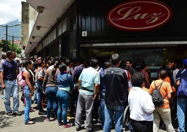 Un grupo de personas hacía fila el miércoles para adquirir alimentos y otros productos básicos en un supermercado de Caracas.
