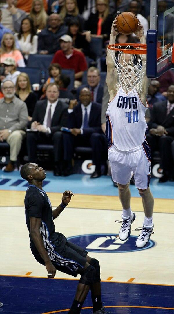 Cody Zeller, de los Bobcats, hunde el balón en la canasta, en partido del viernes pasado ante los Timberwolves de Minnesota. Acá lo observa Gorgui Dieng.