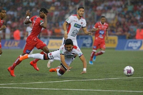 Jonathan Moya (atrás) observa una falta sobre su compañero Barlon Sequeira, quien cae a la gramilla del Santos de Guápiles. Foto: Mayela López