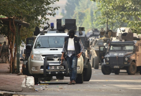 Un policía camina mientras vehículos armados bloquean la carretera que conduce al sitio donde se produjo el tiroteo Diyarbakir. | AP