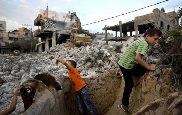 Niños palestinos juegan en medio de los escombros de casas y edificios destruidos en el barrio Shejaiya, en el este de la ciudad de Gaza. | AFP