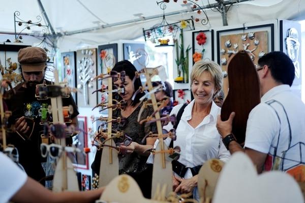 Las personas se acercaban a los toldos para ver el trabajo de los artesanos. Algunos aprovecharon la ocasión y compraban varios artículos. Fotografía: Marcela Bertozzi